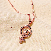 A rose gold necklace with a pink tourmaline stone on a piece of linen