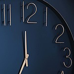 Close-up photo of a navy blue and gold analog clock face