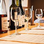 Wine glasses and wine bottles on top of tasting menus